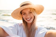 Portrait of positive blonde woman 20s in summer straw hat smilin. G and taking selfie while walking at sea coast Stock Images