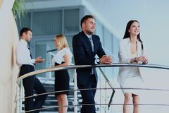 Portrait of positive business group standing on stairs of modern office. Portrait of positive business group standing on stairs of modern office Royalty Free Stock Images