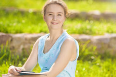 Portrait of a Positive Caucasian Blond Woman Reading Ebook Royalty Free Stock Photo