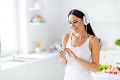 Portrait of positive cheerful girl stay in kitchen listen music on headphones use smartphone want find choice what to