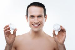 Portrait of a positive cheerful man using cosmetics Royalty Free Stock Photos