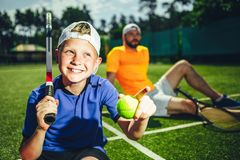 Satisfied kid resting after tennis stock image