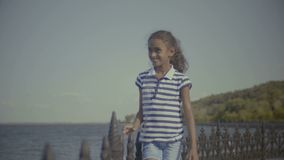 Smiling little african american girl enjoying nature. Portrait of positive cute elementary age african american girl in casual clothes walking along parapet stock video