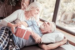 Portrait of positive elderly couple with a present royalty free stock photos