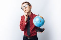 Portrait of a positive and emotional and thoughtful student, with a globe, white background, glasses, red shirt, business theme, a royalty free stock photography
