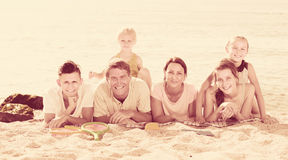 Portrait of positive family lying together on beach Royalty Free Stock Image