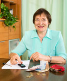 Portrait of positive female pensioner with cash and bills Royalty Free Stock Images
