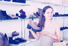 Portrait of positive female selecting loafers. In footgear center Stock Photography