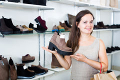 Portrait of positive female selecting loafers. In footgear center Royalty Free Stock Photo