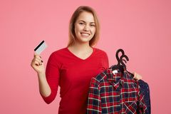 Portrait of positive glad female model holds new clothing and credit card, going to pay for purchase, isolated over pink backgroun royalty free stock photography