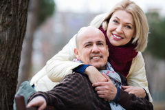 Portrait of positive happy smiling mature couple in city Stock Photos
