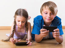 Portrait of positive kids playing with smartphones Stock Photography