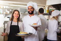 Portrait of positive kitchen workers. Happy chefs and young nippy in apron working at restaurant kitchen Royalty Free Stock Image
