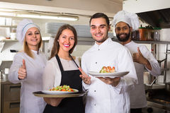 Portrait of positive kitchen workers. Happy chefs and young smiling nippy in apron working at restaurant kitchen. Selective focus Stock Images