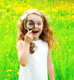 Portrait of positive little girl looking through a magnifying Royalty Free Stock Images
