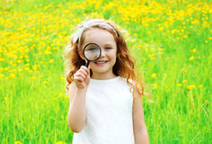 Portrait of positive little girl looking through a magnifying Royalty Free Stock Photo