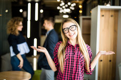 Portrait of a positive looking young woman standing with her open palms with coworkers talking in the background. Portrait of a positive looking young women Stock Image