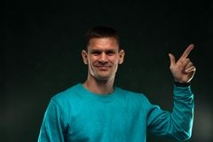 Portrait of positive man in blue sweatshirt. Showing finger on green vintage background Royalty Free Stock Images