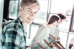 Portrait of positive man while working. Think positive. Handsome blonde office worker keeping smile on his face and turning head while looking at camera royalty free stock images