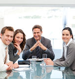 Portrait of a positive manager with his team. Sitting at a table Royalty Free Stock Images