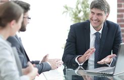 Positive manager with his team sitting at the table Stock Image