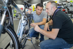Portrait positive men reviewing bicycles at bike store Stock Photo