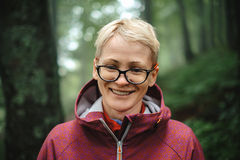 Portrait of positive senior woman in forest stock photography