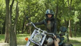 Stylish woman biker ready for ride on motorcycle stock footage