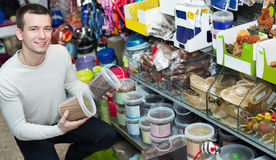 Portrait of positive smiling guy selecting tasty treats. In petshop stock images