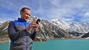 Portrait of positive smiling man uses the using smartphone behind beautifull mountain lake landscape stock video