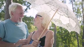 Portrait of positive smiling mature woman in sunglasses standing outdoors under the white parasol. Senior man meeting stock video