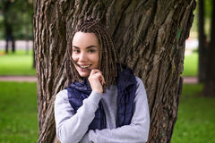 Portrait of a positive teenage girl with braided plaits. She smiles broadly and looks confidently Royalty Free Stock Photography