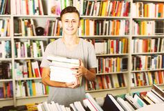 Portrait of positive teenager boy with book pile. In shop Stock Photography
