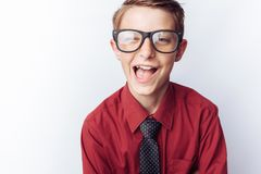 Portrait of a positive teenager on a white background, glasses, red shirt, advertising, text insert. Portrait of a positive teenager on a white background royalty free stock images