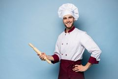 Portrait of positive toothy chef cook in beret, white outfit having tools in crossed arms looking at camera. Portrait of positive toothy chef cook in beret stock image