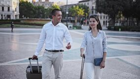 Portrait of elegant young tourist couple walking around summer city with suitcases