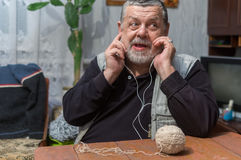 Portrait of positive Ukrainian peasant sitting at wooden table and listening music over headphones Stock Photography