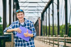 Positive young male student showing thumbs up. Portrait of positive young Caucasian male student wearing checked shirt and sunglasses standing on bridge, holding Stock Images