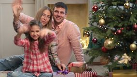 Carefree family of three waving hands at Christmas stock video footage