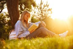 Portrait of a positive young girl sitting on a grass. At the park, reading a book, taking notes Royalty Free Stock Image