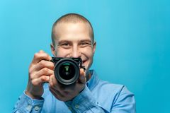 Portrait of positive young male photographer holding camera. Against a blue background stock image