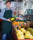 Portrait of young man working in grocery. Portrait of positive young male posing with melon in grocery and smiling Stock Photography
