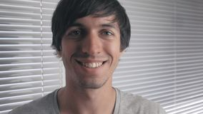 Portrait of positive young man smiling against the background of office blinds. Portrait of a young man smiling against the background of office blinds stock video footage
