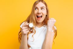 Portrait of a positive young woman, pointing her finger at the clock, on a yellow background stock photo