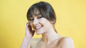Portrait of positively emotional girl on the yellow background in 4K stock footage