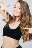 Positivity sporty girl pointing by finger on black top. Portrait of positivity and pretty girl smiling at camera and pointing by finger at herself on black top royalty free stock images