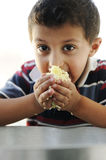 Portrait of poverty, little poor boy. On food pot eating rice royalty free stock image