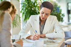 Female Business Leader Signing Papers stock image