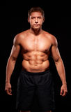 Portrait of a powerful shirtless athletic man on black background Stock Photos