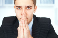 Portrait of praying young businessman Royalty Free Stock Images
